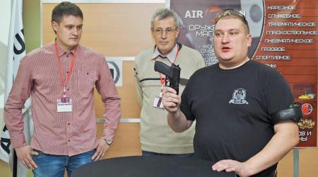 Представитель Федерации практической стрельбы Московской области Александр Попов (спистолетом вруках) делится сучастниками мероприятия первыми впечатлениями отэксплуатации спортивного пистолета Р226ТК