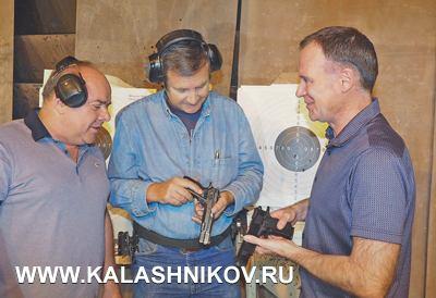 Евгений Ефимов (вцентре) иАндрей Груздев обсуждают новые пистолеты сруководителем концерна «Русское оружие» Иваном Сапрыкиным