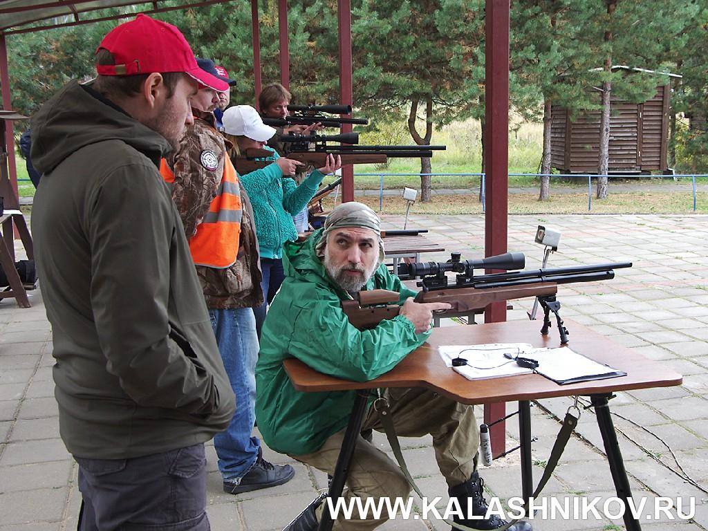 Инструктор по варминтингу Роман Онищенко показывает способ удержания винтовки при стрельбе сидя с сошки. Иллюстрация в журнале «КАЛАШНИКОВ»