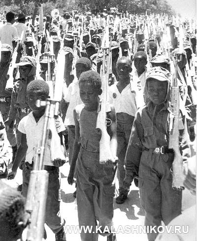 Танзанийские подростки маршируют с муляжами карабинов СКС. Журнал Калашников