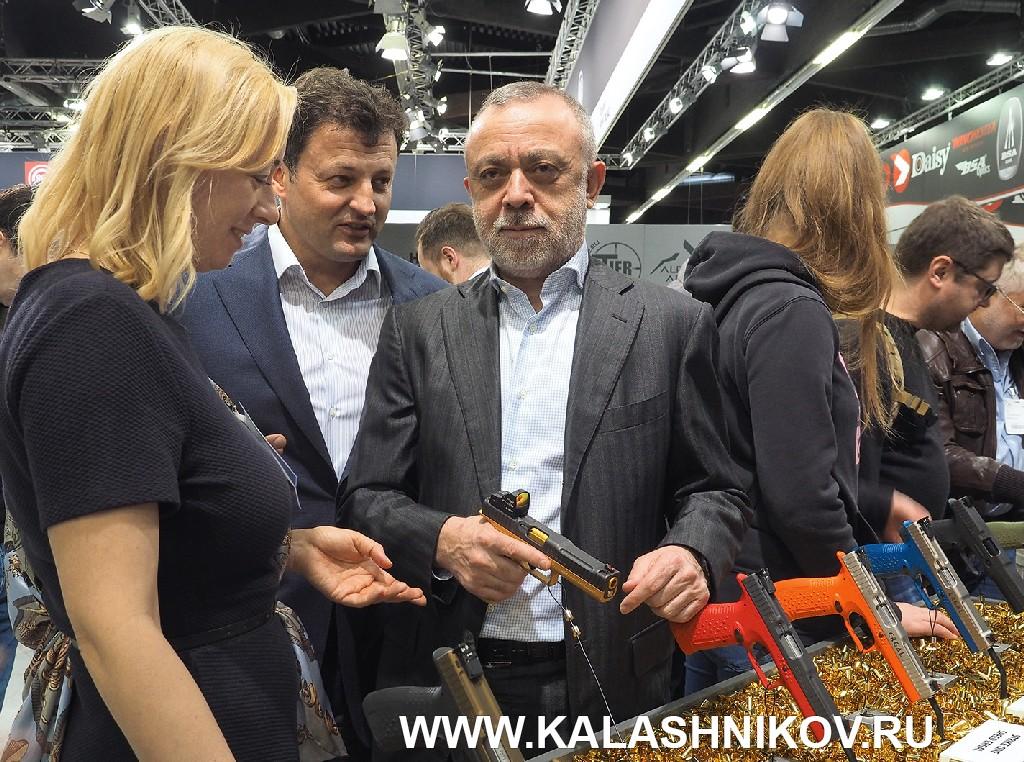 Михаил Гущин, Анастасия Черненко и Арсен Чомаев на стенде с пистолетами Stryke One на выставке IWA 2019